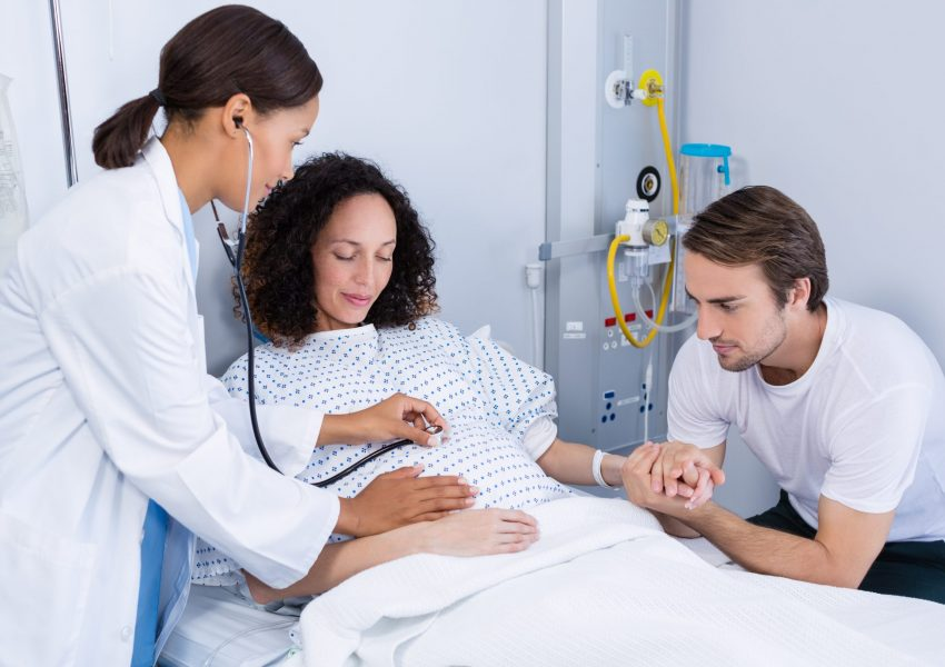 Doctor examining pregnant woman in ward of hospital