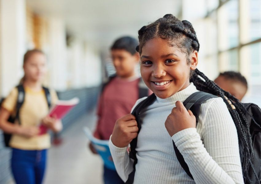 Portrait of a confident young girl standing in the hallway of school with her peers in the background